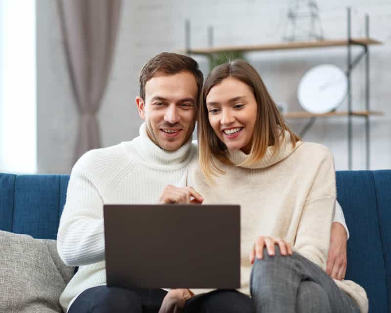couple filling out paperwork online on laptop