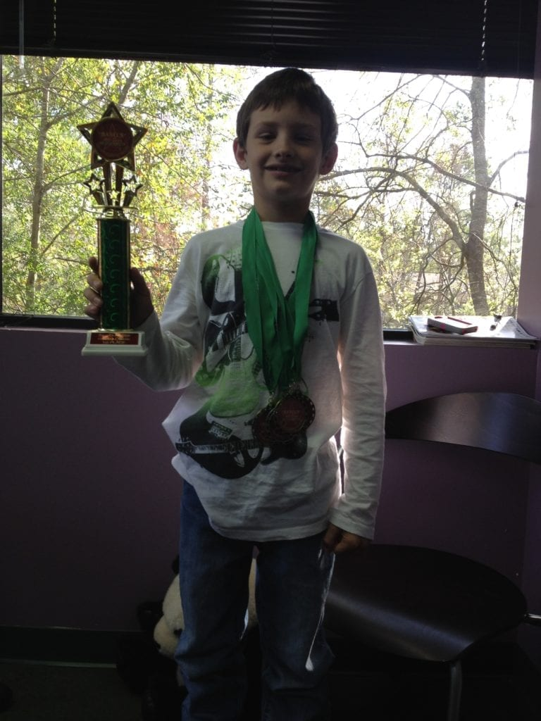 young boy with trophy