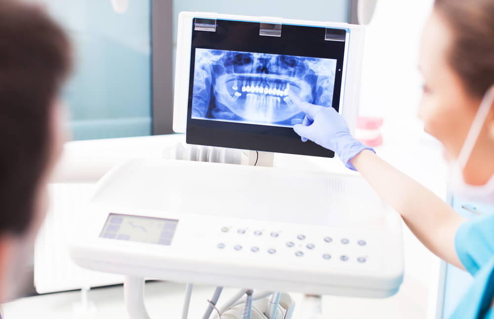 dentist showing patient dental x-ray