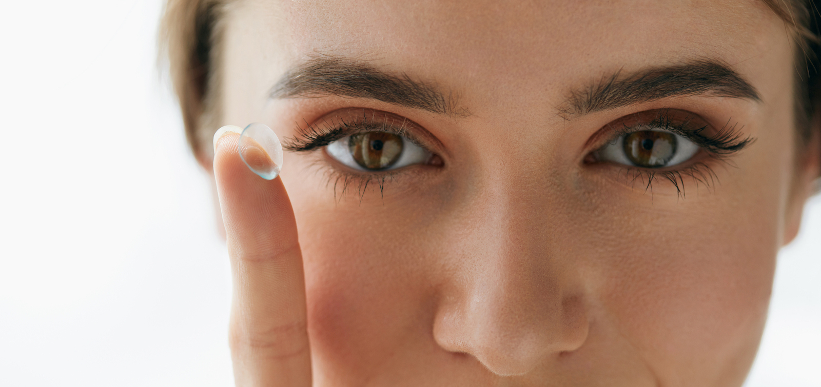 Close up of woman holding a contact lens