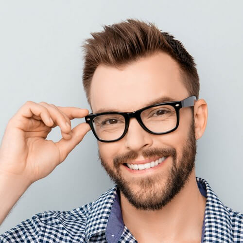 Man smiling holding his glasses