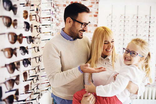 Family picking out glasses for daughter