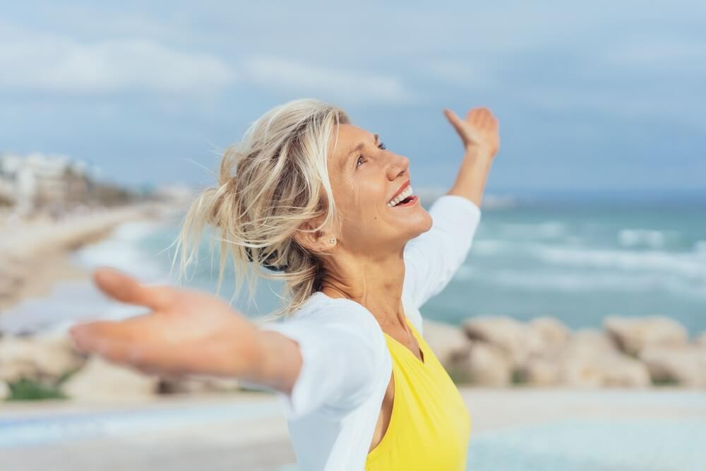 woman smiling with arms stretched out on the beach
