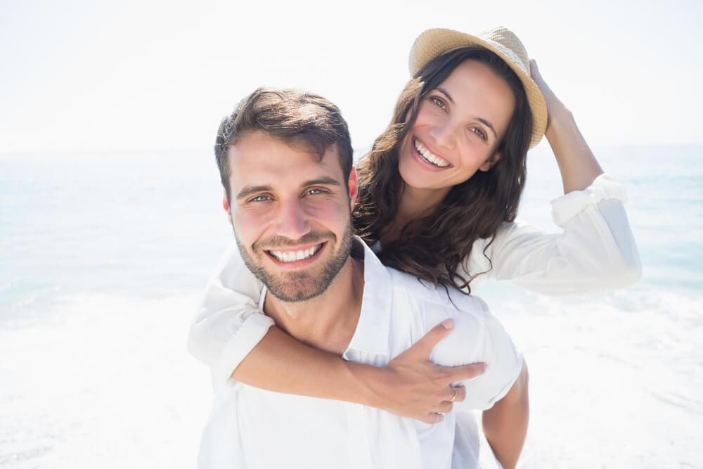 young attractive couple at a flordia beach after dental work