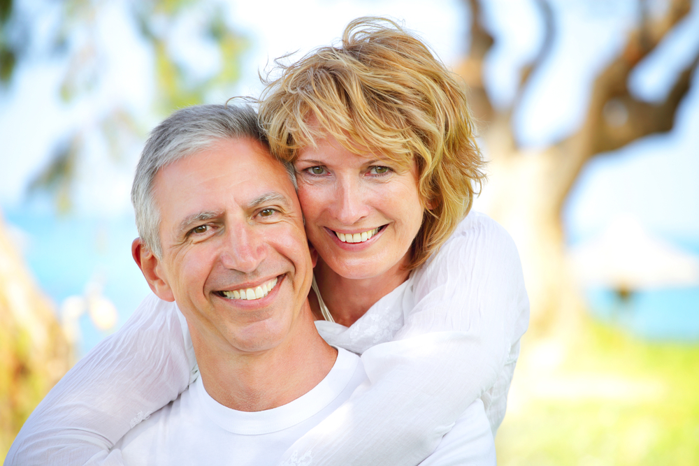 couple smiling on isolated background after having arestin treatment